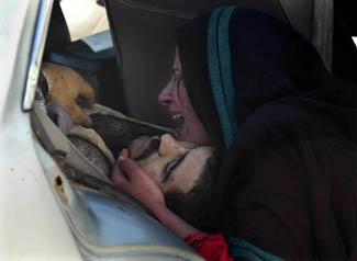 An Iraqi woman grieves for her husband as she finds him dead as they reach the hospital where she rushed him after he was caught in crossfire on the day Saddam fell in Iraq ©Ruth Fremson/The New York Times
