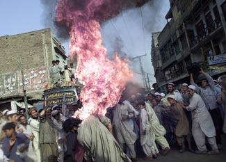 A Pakistani man sets himself on fire accidentally as he tries to light an American flag on fire during an anti-American protest 2001    ©Ruth Fremson/The New York Times